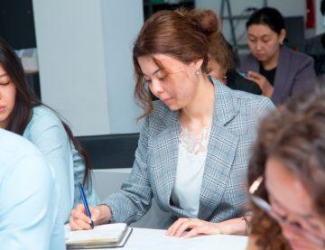 Джульетта Базеян с красивой прической пишет на блокноте